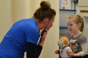 Medical assisting student and child with teddy bear